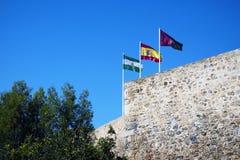 Três bandeiras: Espanha, Andolusia e Malaga na parede defensiva da fortaleza Fortaleza árabe Gibralfaro espanhol Castillo de Patí fotografia de stock