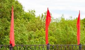 Três bandeiras vermelhas que vibram ou que acenam no vento Decoração festiva da ponte fotografia de stock