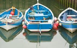 Três barcos de pesca azuis pequenos. fotografia de stock royalty free