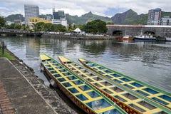 Três barcos originais coloridos longos amarrados em um porto Foto de Stock