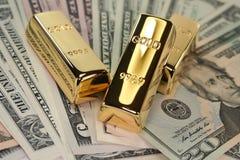 Três barras de ouro em contas de dólar fotografia de stock royalty free