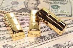 Três barras de ouro em contas de dólar Imagens de Stock Royalty Free