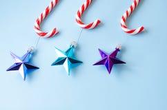 Três bastões de doces com os brinquedos na árvore de Natal imagem de stock royalty free