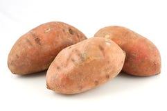 Três batatas doces isoladas no fundo branco imagens de stock royalty free