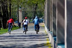 Três bicicletas de montada dos povos no parque Fotografia de Stock