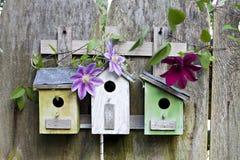 Três birdhouses na cerca de madeira velha imagens de stock