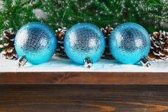 Três bolas azuis do ano novo encontram-se em uma prateleira marrom de madeira cercada por ramos do abeto Fotos de Stock