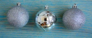 Três bolas brilhantes do Natal no fundo de madeira verde Fotos de Stock