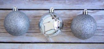 Três bolas brilhantes do Natal no fundo de madeira verde Fotos de Stock Royalty Free