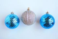 Três bolas brilhantes do Natal no fundo de madeira verde Fotografia de Stock Royalty Free