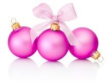 Três bolas cor-de-rosa do Natal com a curva da fita isolada no branco Foto de Stock