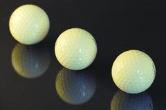 Três bolas de golfe em um fundo preto Imagens de Stock