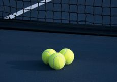 Três bolas de tênis em um campo de tênis imagens de stock