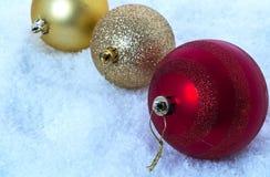 Três bolas do Natal na neve Tonificação fria Foto de Stock