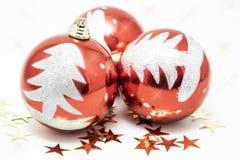 Três bolas vermelhas decoradas com uma árvore de prata do brilho para o Natal junto com estrelas douradas foto de stock royalty free