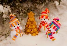 Três bonecos de neve com a árvore verde dourada Imagens de Stock Royalty Free