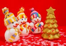 Três bonecos de neve com a árvore verde dourada Imagem de Stock