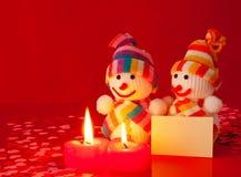 Três bonecos de neve com duas velas ardentes Foto de Stock