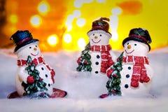 Três bonecos de neve de sorriso na neve, ano novo feliz 2017, Natal Fotos de Stock Royalty Free