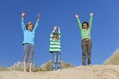 Três braços das crianças levantados tendo o divertimento na praia Foto de Stock