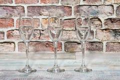 Três cálices de vidro vazios em uma placa de madeira rústica Fotografia de Stock Royalty Free