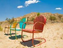 Três cadeiras coloridas esquecidas no deserto Imagens de Stock