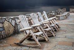 Três cadeiras de balanço de madeira que sentam-se na almofada do cimento imagem de stock