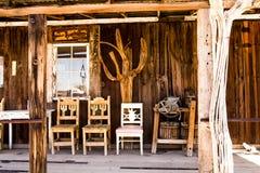 Três cadeiras de madeira em Front Porch de uma loja velha do tempo fotografia de stock