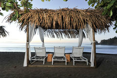 Três cadeiras de sala de estar em uma praia coberta Imagem de Stock