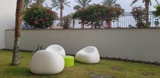 Três cadeiras plásticas brancas ficam vazias em volta de uma tabela pequena na grama foto de stock