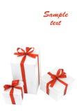 Três caixas de presente brancas com curvas vermelhas Fotografia de Stock Royalty Free