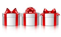 Três caixas de presente brancas com curvas vermelhas. Foto de Stock Royalty Free