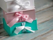 Três caixas de presente, brancos, rosa e turquesas Fundo de madeira Fotografia de Stock Royalty Free