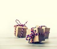 Três caixas de presente feitos a mão no fundo brilhante da cor Fotos de Stock Royalty Free