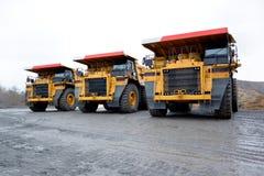 Três caminhões basculantes pesados para o transporte de bens na pedreira Fotografia de Stock