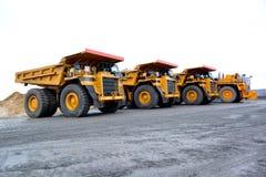Três caminhões basculantes pesados para o transporte dos bens no q Imagens de Stock Royalty Free