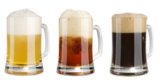 Três canecas de cerveja multicolor do álcool sobre o branco Fotos de Stock Royalty Free