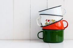 Três canecas esmaltadas coloridas brilhantes Imagens de Stock Royalty Free