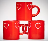 Três canecas vermelhas com sinais do amor Foto de Stock