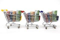 Três carros de compra com dinheiro em uma fileira Imagens de Stock