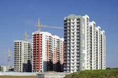 Três casas e três guindastes de construção Fotografia de Stock
