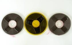 Três cassetes áudio em um carretel de cores diferentes, em um fundo branco foto de stock
