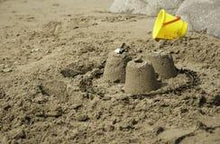Três castelos de areia simples com cubeta amarela Imagem de Stock Royalty Free