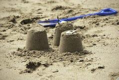Três castelos de areia simples com pá azul Foto de Stock