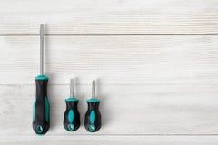 Três chaves de fenda com bocais diferentes e o tamanho estão na superfície de madeira Fotografia de Stock