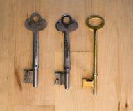 Três chaves diferentes na madeira Foto de Stock