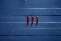 Três chilis encarnados na tabela de madeira azul Fotografia de Stock Royalty Free