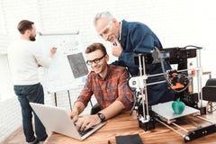 Três cientistas são envolvidos nas impressoras 3D da fundação e tornar-se As pessoas idosas equipam controles o trabalho de sua e Foto de Stock