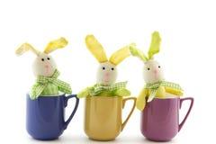 Três coelhinhos da Páscoa do brinquedo em uma xícara de chá Fotos de Stock Royalty Free