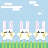 Três coelhos no gramado com os ovos da páscoa nas embreagens ilustração do vetor